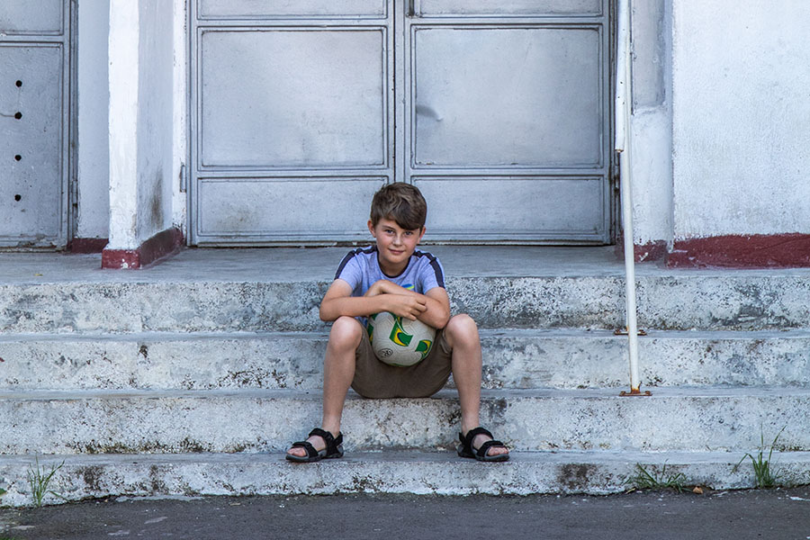 Boy holds his ball and sits down outside his flat in Romania waiting